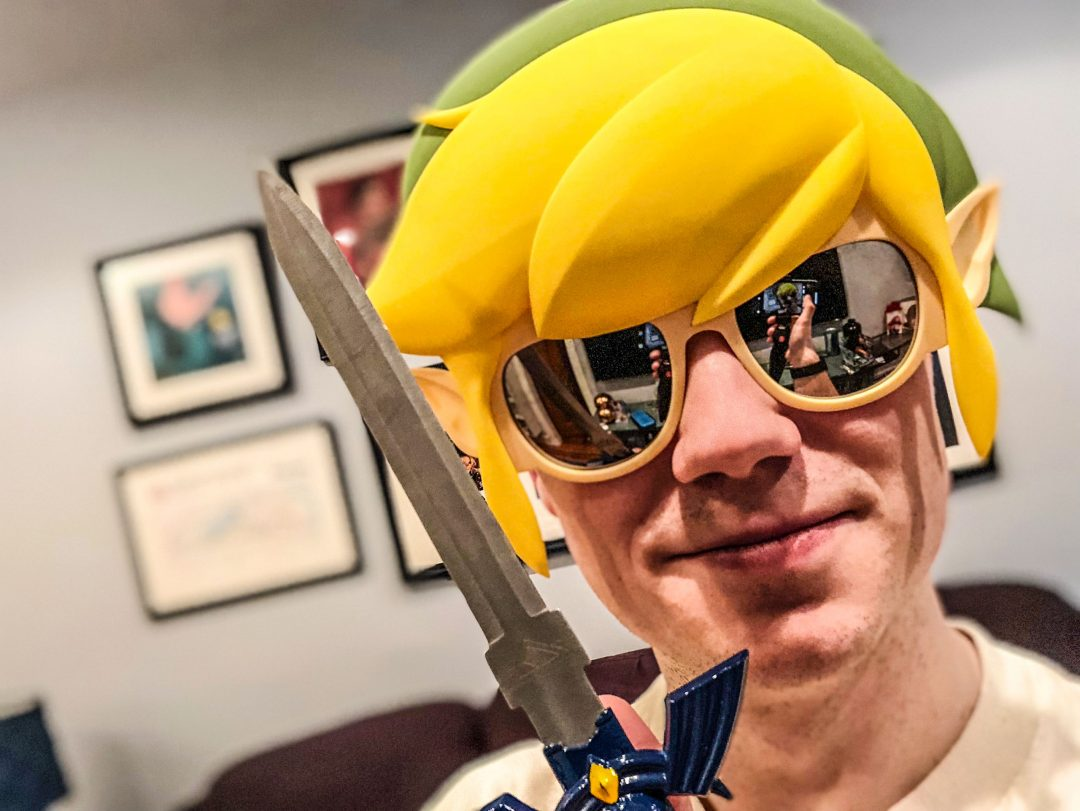 Me, wearing a Link sunglasses mask and holding the Master Sword